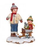 Village de Noël miniature, garçon et petit frère sur luge