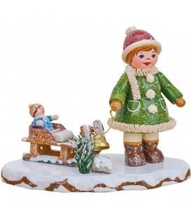 Village de Noël miniature, fillette avec petit frère sur luge